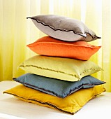 Stack of colourful cushions in front of yellow curtain