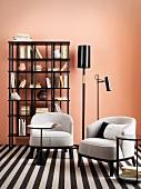 Zwei helle Polstersessel auf schwarz-weißem Teppich vor Bücherregal und lachsfarbener Wand