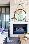 Round mirror hangs on the stone wall above the fireplace with rope