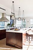 Three hanging lights above the dark wood kitchen island
