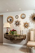 Antique wall-mounted console below various sunburst mirrors