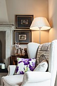 Floral scatter cushion on wing-back chair in front of standard lamp in corner