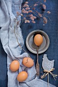 Hen ornament, eggs, vintage spoon and pewter plate on blue fabrics