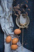 Eggs, hen ornament and pewter plate on blue fabrics