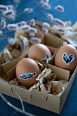 Easter eggs decorated with animal stickers in vintage cardboard box