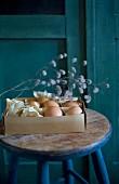 Vintage Pappschachtel mit Eiern und Trockenzweig auf Holzhocker