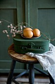 Eggs and on pewter plate on top of miniature vintage suitcase