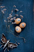 Easter eggs decorated with animal stickers, dried twigs and metal insect figurine on dark blue fabric