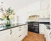 Naturweisse Landhausküche mit Küchentheke, Granitarbeitsplatte und schwarzem Gasherd