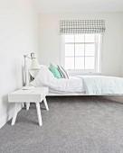 Weisses Bett und Nachtkästchen auf grauem Teppichboden