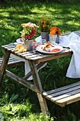 Sommerliches Gedeck für Zwei mit farbenfrohen Blumensträusschen im Garten