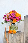 Colourful bouquet of zinnias and tagetes in glass vase on wooden block
