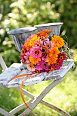 Colourful bouquet of zinnias and tagetes in glass vase on vintage garden chair