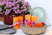 Orange candles decorated with flowers and ribbons in rustic bowl