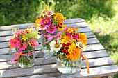 Colourful posies of zinnias and tagetes on rustic garden table