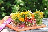 Mehrere Tischblumensträußchen mit Gartenblumen in Gläsern auf verpacktem Geschenk arrangiert