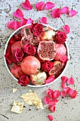Pomegranates and roses in bowl