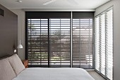 Bedroom with sunshades on glass walls and double bed against dark brown wall