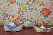 Colourful paper boats in front of floral wallpaper