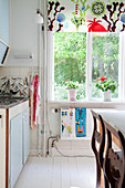 Colourful roller blind on window in vintage-style kitchen-dining room
