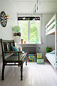 Wooden bench and bunk beds in children's bedroom