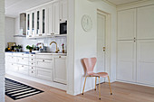 Pink chair next to open doorway leading into white country-house kitchen