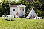 Wendy house, wigwam and children's furniture on lawn in sunny garden