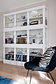 Zebra-patterned cushion on black easy chair in front of glass-fronted cabinets