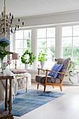 Scandinavian-style living room with row of large windows overlooking garden