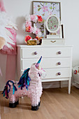 Unicorn pinata in front of chest of drawers decorated with number 5 made from paper flowers
