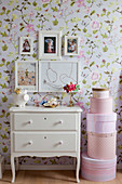 Pictures above vintage-style chest of drawers and stacked pink hat boxes