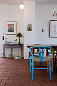 Blue designer chair at dining table on terracotta floor tiles