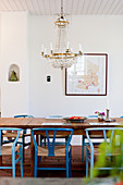 Chandelier above dining table and blue designer chairs