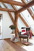 Leather armchair and cushion with red felt hedgehog motif in cosy reading corner in converted attic