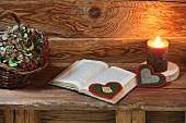 Hand-crafted, heart-shaped felt bookmark next to lit candle on rustic wooden bench