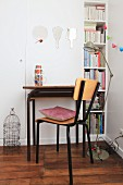 Retro desk and chair in front of white fitted cupboard with bookshelves at one side