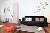 Offener Wohnbereich mit schwarzer Couch, Kohlenschütte, rosafarbenem Retroschrank und orangefarbenem Sitzpouf
