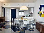 View past dining table into open-plan kitchen with hexagonal floor tiles