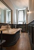 Schmales Badezimmer mit Wandverkleidung und großem Spiegel