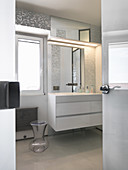 Bright bathroom with silver mosaic tiles and white furniture