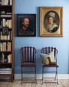 Zwei Portraitgemälde mit antikem Flair in verschiedenen Rahmen an hellblauer Wand
