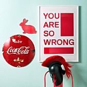 Red typographic print in white frame, red rabbit silhouette and vintage advertising sign on wall