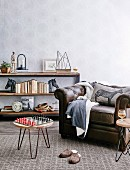 Vintage leather armchair, side table with chess board and shelf with books and decorative objects against a wall with patterned wallpaper