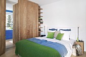 Alpine-style bedroom with blue and green accents and wooden elements