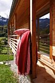 Kariertes Bett hängt vom Balkon eines modernen Holzhauses