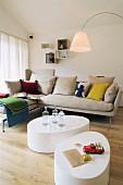 Zwei organisch geformte Couchtische vor einem Sofa mit bunten Kissen