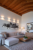 Large picture of bulls above sofa in living room with wood-beamed ceiling