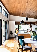 Open kitchen and dining area with parquet flooring, wooden ceiling and patio door, mother and son in the background