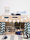Boy's room with loft bed and white pennant chain, soft toys, pillows and sayings