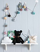 Black, knitted cuddly toy on a white wall shelf under a colorful pompom chain on wooden paneling